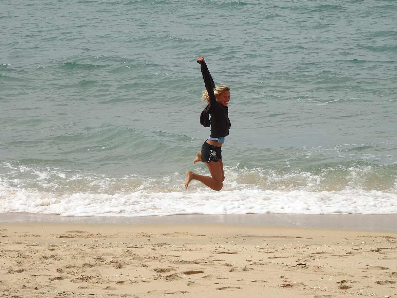 FLASHPACKER | Karin fröhlich springend am Strand in Australien