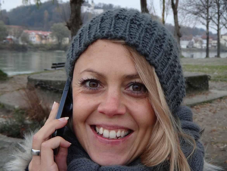 FLASHPACKER | Karin mit Mütze und Telefon am Ohr in Passau in Deutschland