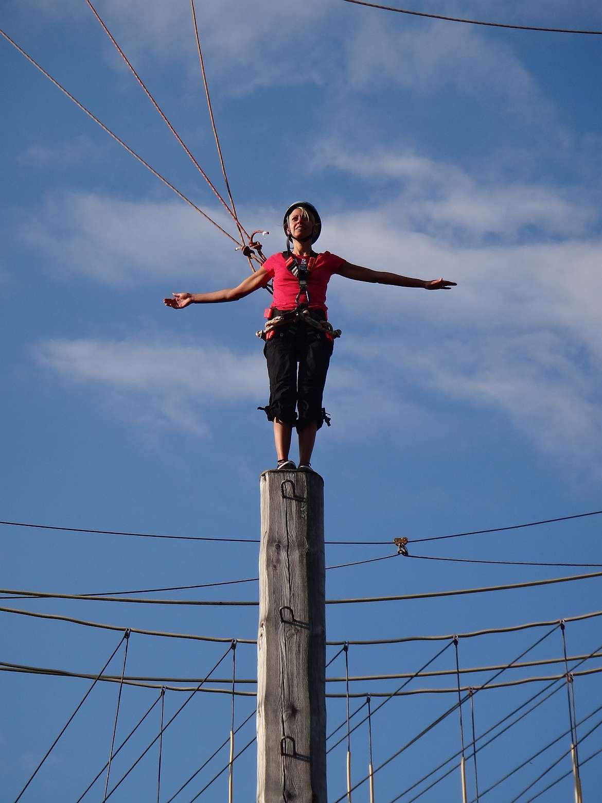 FLASHPACKER | Karin auf einem 8m Pfahl im Hochseilgarten am Tegernsee in Deutschland