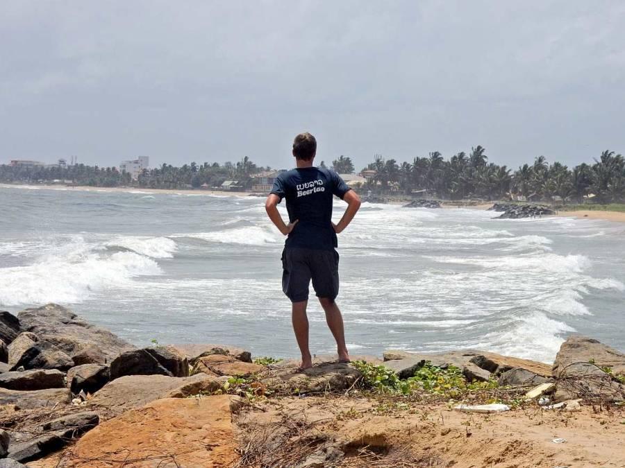 Henning steht in Sri Lanka auf einem Felsen am Stadtrand Negombos und blickt auf die starke Meeresbrandung des Negombo Beaches.