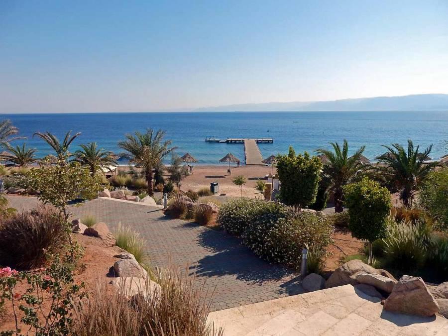 Jordanien | Berenice Beach Club in Aqaba. Blick von oben auf das Meer hinweg über den angelegten Garten mit Palmen und den Strand samt Sonnenschirmen und -stühlen
