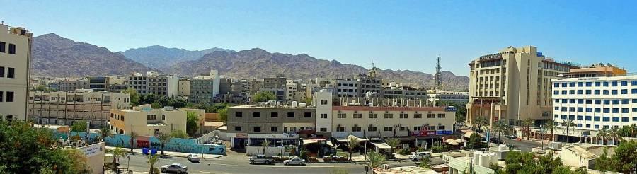 Jordanien | Das Stadtzentrum in Aqaba fotografiert vom Balkon unseres Hotels als Panorama. Shops, Restaurants und Häuser der Stadt vor einer Bergkulisse der Wüste