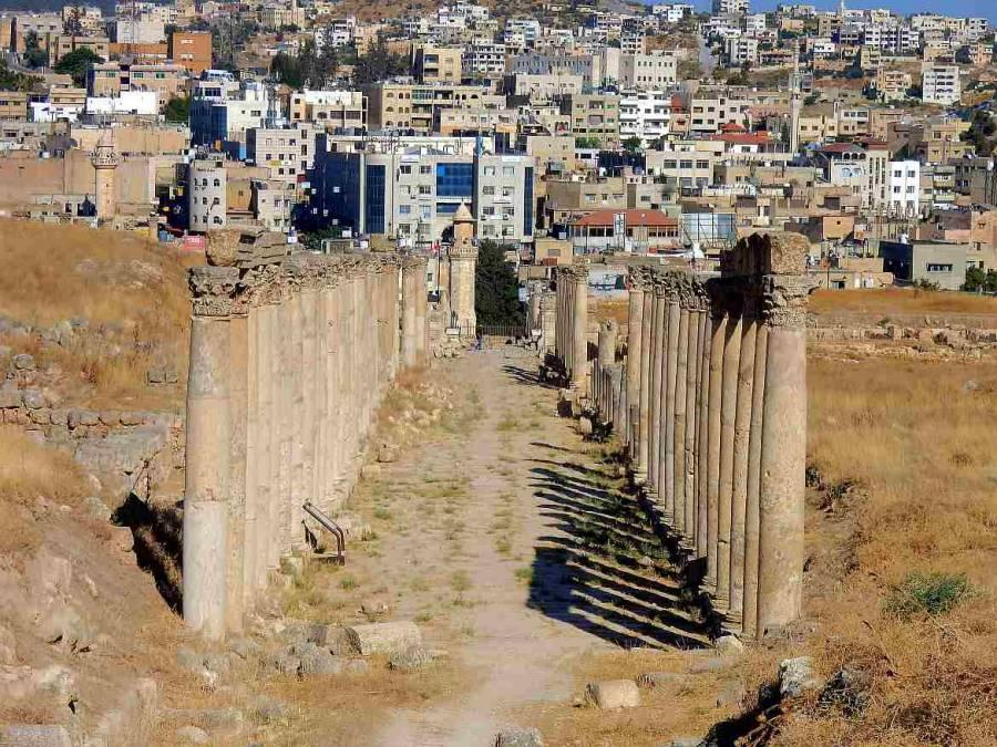 Jordanien | Jerash erhaltene Säulen der antiken Stadt im Vordergrund und im Hintergrund die neu gebauten flachen viereckigen Häuser der neue Stadt