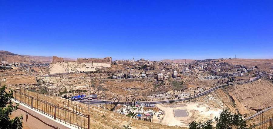 Jordanien | Panoramablick auf die Kreuzritterburg, einige Häuser und die Panoramastraße in Karak bei blauem Himmel