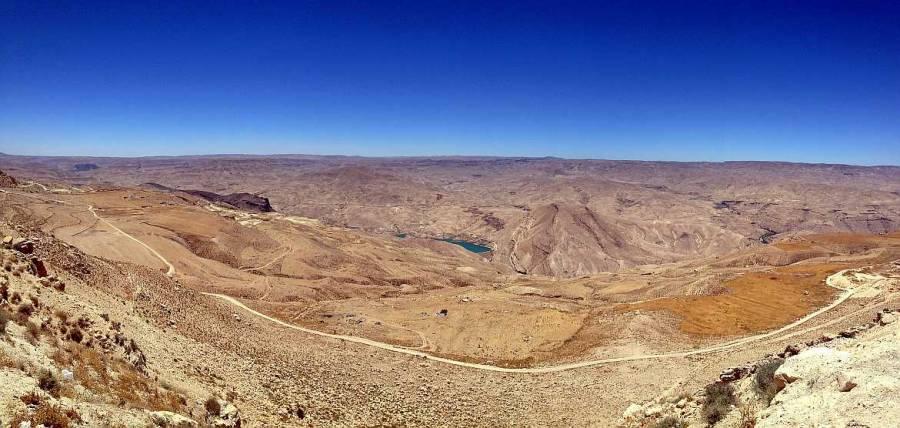 Jordanien | Panorama vom Kings Highway auf dem Weg von Madaba nach Petra. Blick auf gelblich und braune Berge und eine sattblauen Stausee bei blauem Himmel