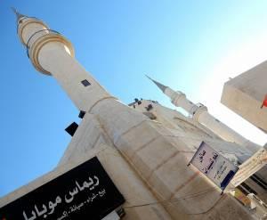 Jordanien | Moschee in Madaba. Zwei Spitze weiße Türme und arabische Schriftzeichen vor blauem Himmel