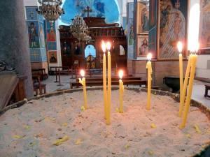 Sehenswürdigkeiten & interessante Orte | Eindrücke aus der St. Georgs Kirche in Madaba. Brennende Kerzen in ein mit Sand gefülltes rundes Becken gesteckt und Blick auf den Altar