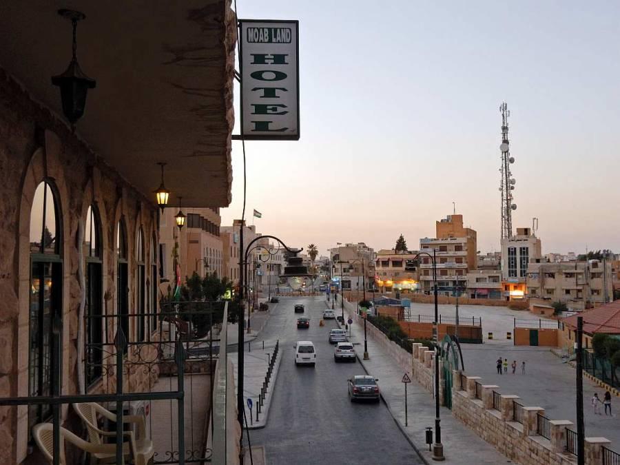 Jordanien | Madaba Stadtblick vom Balkon des Moab Land Hotel auf die vorbeiführende Straße und einige Häuser der Stadt bei Sonnenuntergang