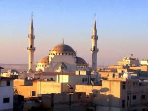 Sehenswürdigkeiten & interessante Orte | islamische Moschee in Madaba von oben fotografiert. Zwei spitze Türme und drei runde Kuppeln inmitten einfach und flach gebauter Häuser der Stadt