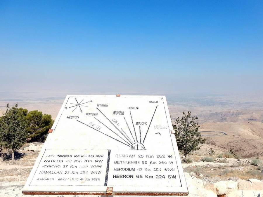 Jordanien | Blick Richtung Totes Meer, Israel und Westjordanland (Jericho, Ramallah und Bethlehem) vom Mount Nebo. EIne weiße Steintafelzeigt die Richtungen und Entfernung