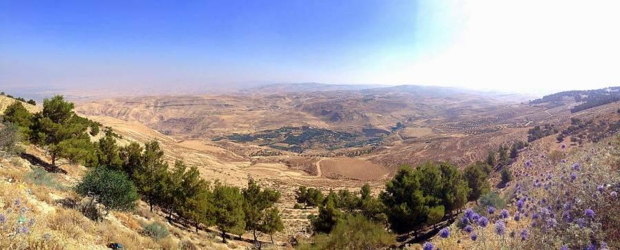 Jordanien | Panoramablick vom Mount Nebo ins gelobte Land. Eine hügelige bunte Landschaft bei strahlend blauem Himmel