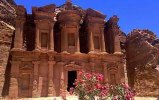 Jordanien | Kloster Ad Deir in Petra fotografiert aus der Nähe. Im Vordergund pinker Rhododendron vor den mächtigen roten Säulen des Eingangs zum Kloster