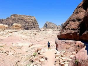 Petra Weltwunder | Panoramablick auf dem Weg zum Kloster AD Deir in der antiken Felsenstadt. Henning von hinten in die Ferne blickend vor einer rot gefärbten Bergkette