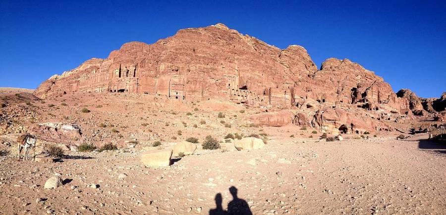 Jordanien | Panoramablickk in der Felsenstadt Petra auf die in den Bergen liegenden Königsgräber. Karin und Hennings Schatten im Vordergrund, blauer Himmel und rote Steinsformationen