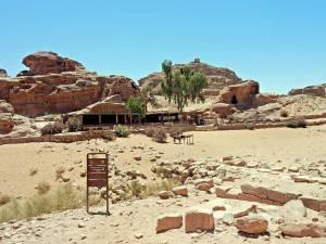 Jordanien | Platz und Cafe auf dem Berg vor dem Kloster Ad Deir. Eine Ebene aus rotem Sand un dSteinen, bei blauem Himmel, im Hintergund ein kleines Restarant und die Sitzplätze im freien umgeben von Bergen