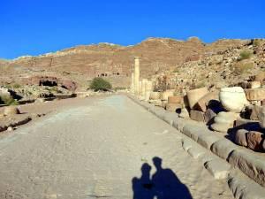 Jordanien | Hauptweg vom Museum Richtung Königsgräber bei blauem Himmel. Ein flacher sandiger Weg führt gerade vorbei an einigen erhaltenen Säulen zu den in den Bergen liegenden Gräbern