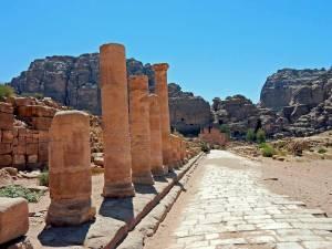 Jordanien | Der Hauptweg im Weltwunder Petra mit Blick Richtung Kloster Ad Deir. Ein flacher sandiger Weg führt gerade vorbei an einigen erhaltenen Säulen zu den in dem auf dem Berg liegenden Kloster