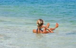Jordanien | Karin aufgrund des hohen Salzgehalt im Wasser sitzend beim Baden im Toten Meer