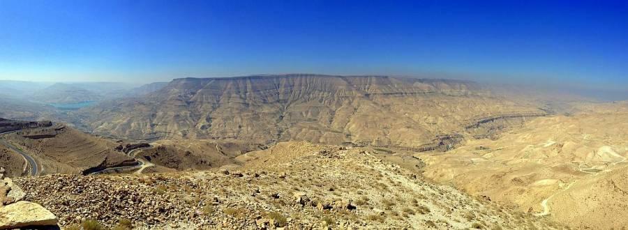 Jordanien | Panoramablick auf Wadi Mujib, der am tiefsten gelegene Canyon der Welt. EIne gelbfarbene bergige Wüste mit Stausee bei blauem Himmel