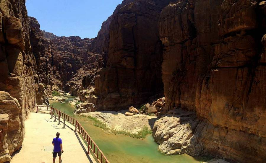 Jordanien | Henning auf einer Wanderung durch den Wadi Mujib Canyon. Rote Bergformationen führen entlang eines grünen Flusses