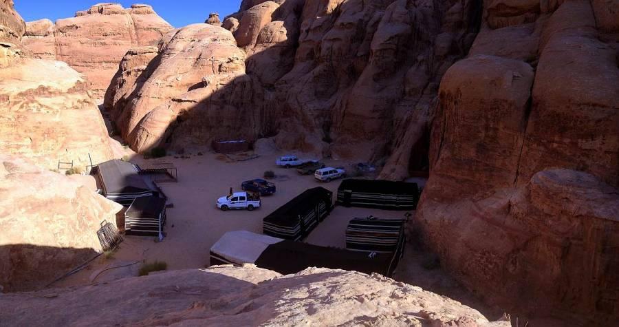 Jordanien | Das Beduinencamp von Bedouin Directions gehört zu unseren Tipps im Wadi Rum. Blick von oben auf das Camp. Zelte und Jeaps umgeben von Wüstenbergen
