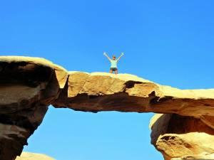 Jordanien | Karin mit den Händen in der Höhe auf dem kleinen Um Fruth Bogen im Wadi Rum