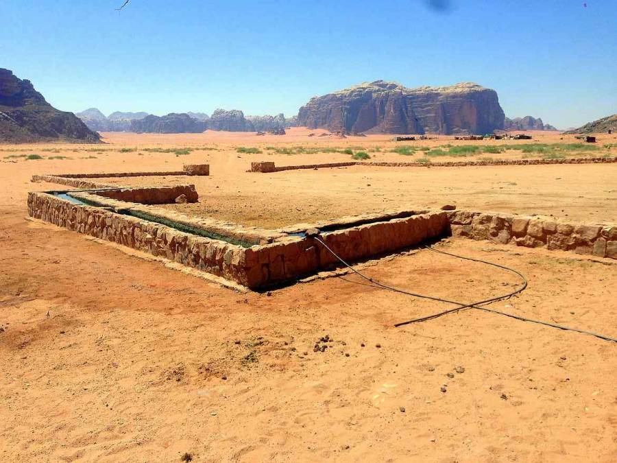 Jordanien | Lawrence Quelle im Wadi Rum. Aus Steinen geformte Wasserstelle für die Kamele der Wadi Rum, umgeben von Bergen bei blauem Himmel und rotem Wüstensand