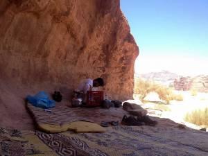 Jordanien | Unser Mittagspause im Wadi Rum. Unser Guide bereitet das Essen, während wir die Stille der Wüste genießen. In einem schattigen Felsvorsprung liegen Matten auf dem Boden, mit Blick auf eine gegenüberliegende Bergkette