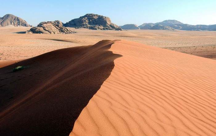 Jordanien | Eine von vielen Sanddünen im Wadi Rum. Ein kleiner Hügel aus rotem Wüstensand im Hintergrund eine Bergkette bei strahlend blauem Himmel
