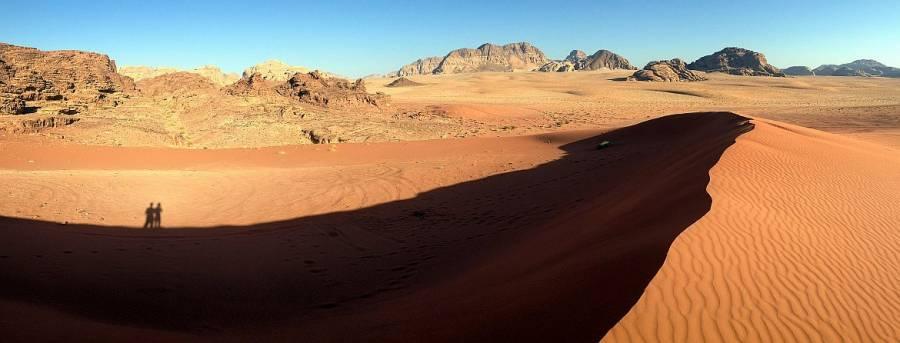 Jordanien | Panorama einer großen Sanddüne im Wadi Rum. Ein großer roter Sandhügel umgeben von Bergen, blauem Himmel und strahlender Sonne, die ihren eigenen und den Schatten von Karin und Henning abzeichnet