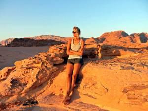 Jordanien | Karin beim Sonnenuntergang im Wadi Rum auf einem kleinen Berg beleuchtet von den letzten Sonnenstrahlen