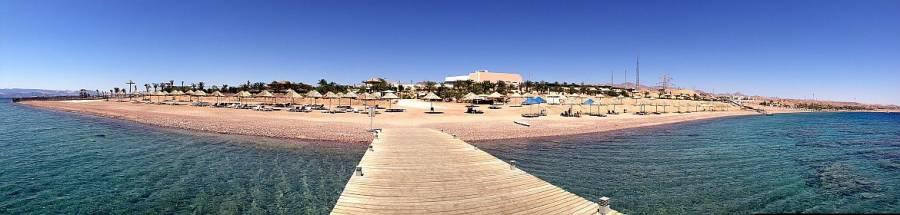 Jordanien | Berenice Beach Park in Aqaba. Blick vom Steg im Wasser aus auf den Strand, Sonnenschirme und- stühle und die Anlage des Parks.