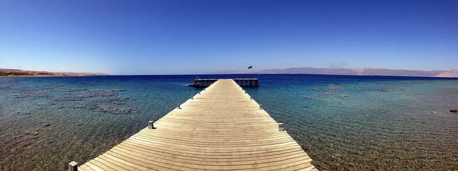 Jordanien | Schnorcheln am Roten Meer im Berenice Beach Park in Aqaba. Ein hölzerner Steg führt ins kristallklare Wasser bei strahlend blauem Himmel