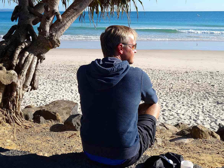 FLASHPACKER | Henning im blauen Kapuzenpulli und Sonnenbrille in Australien am Strand als Denker mit Blick auf den Leuchtturm von Byron Bay