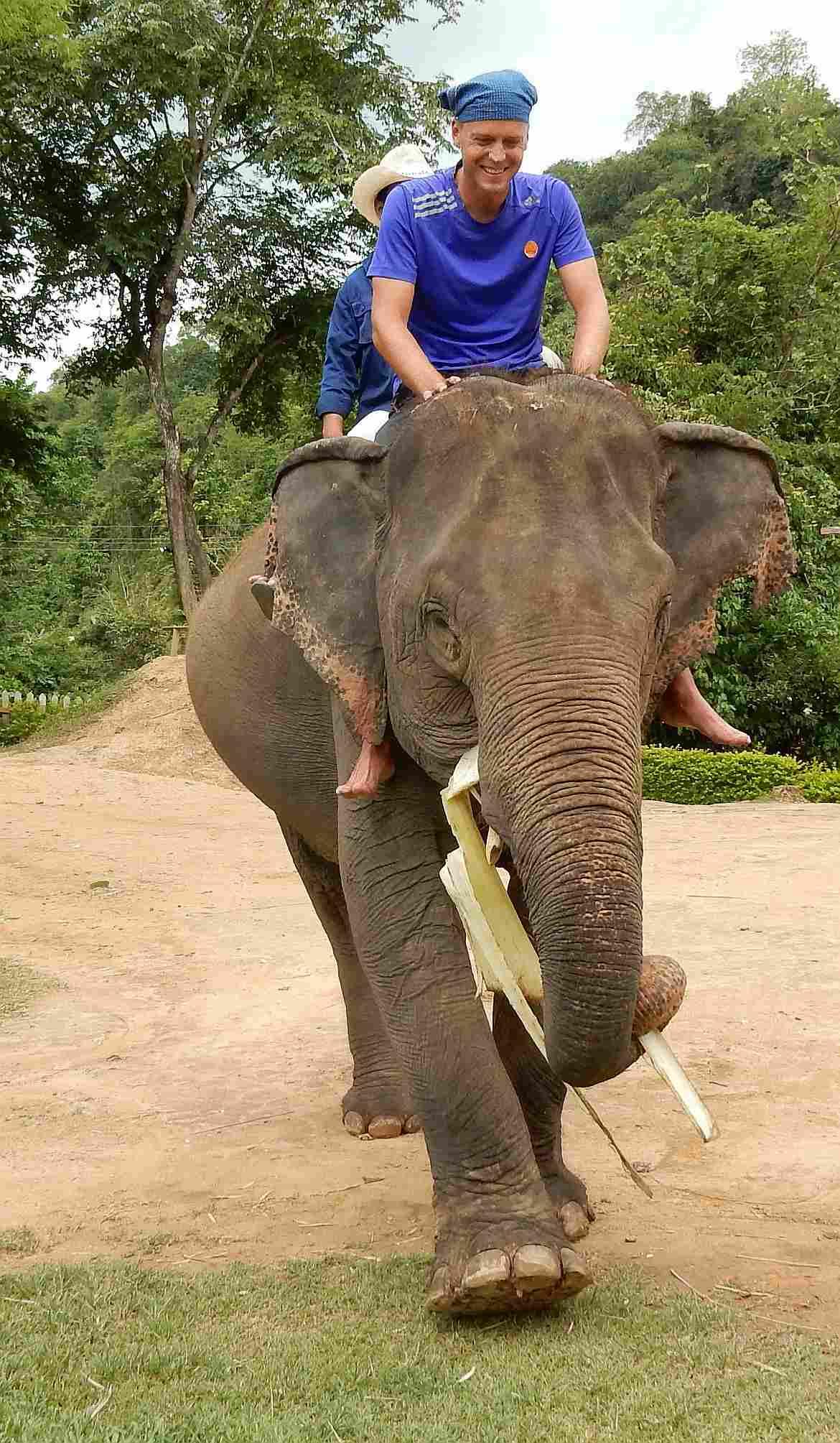 FLASHPACKER | Henning lächelnd auf dem Rücken eines Elefanten in Laos