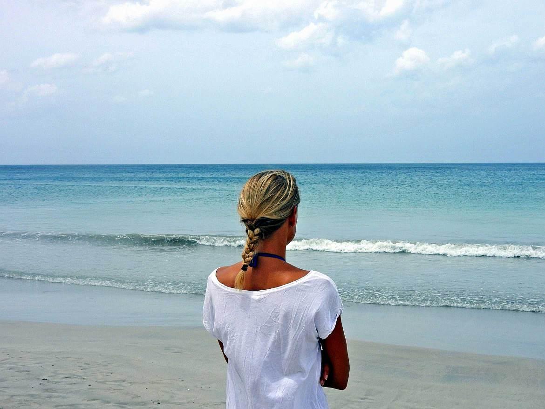 FLASHPACKER | Karin von hinten auf den Horizont des türkisfarbenen Meeres blickend am Strand von Trincomalee in Sri Lanka