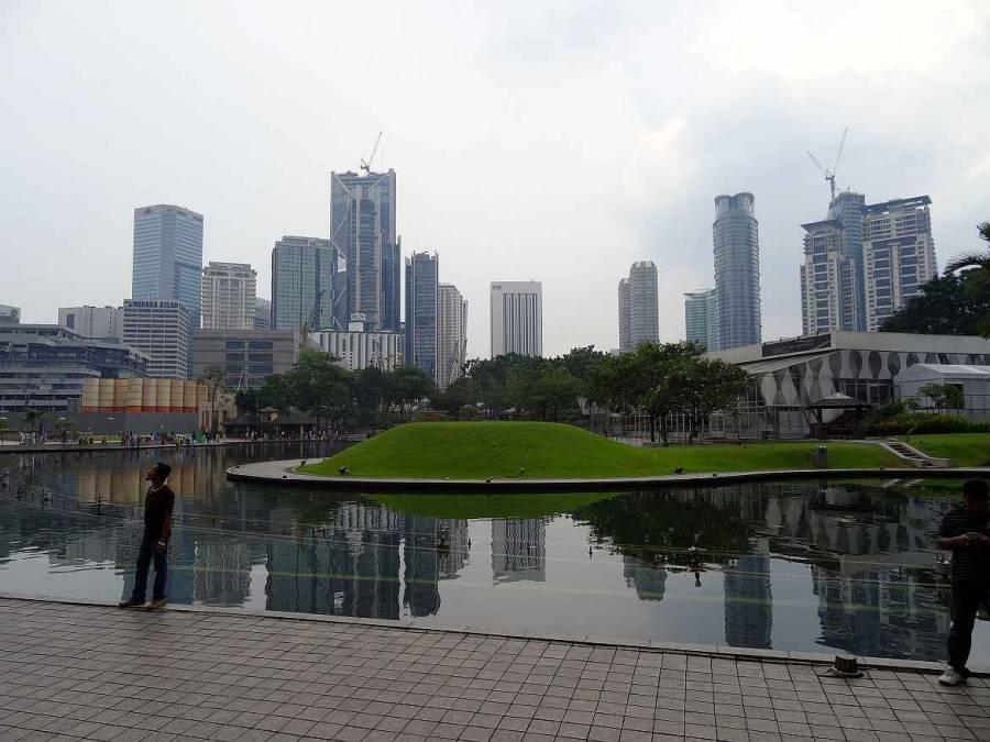 Malaysia | Kuala Lumpur Downtown. Blick durch einen Park mit einem Wasserbecken auf Hochhäuser der Stadt