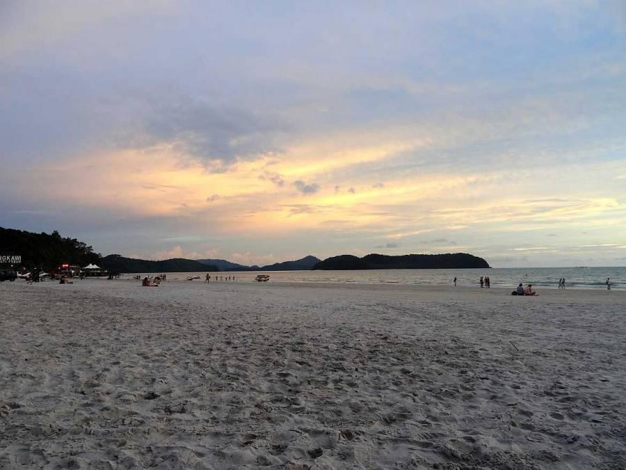 Malaysia | Blick über den Pantai Cenang Strand auf das Meer mit blau, rosa und gelblichem Himmel bei Sonnenuntergang