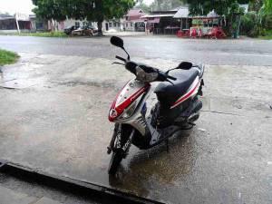 Malaysia | Unser Roller auf Langkawi in schwarz, rot und weiß ist sehr modern und gut erhalten. Geparkt am Straßenrand während eines Regenschauers. Beachte unsere Tipps zum Roller mieten