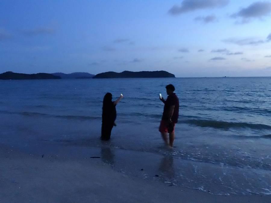 Malaysia | Eindrücke am bekanntesten Strand Pantai Cenang nach Sonnenuntergang. Ein Mann und eine Frau im Kopftuch stehen im Wasser und halten ihre hellleuchtenden Mobilgeräte in die Luft