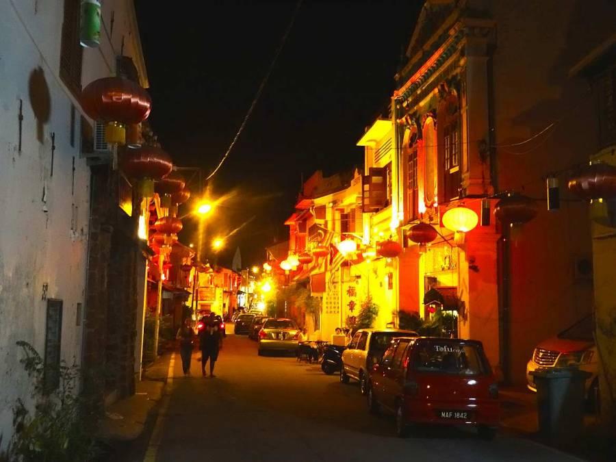 Malaysia | die Altstadt von Melaka bei Nacht. Straßenlampen erleuchten die Häuserreihe und ein paar Spaziergänger in einer kleine Gasse