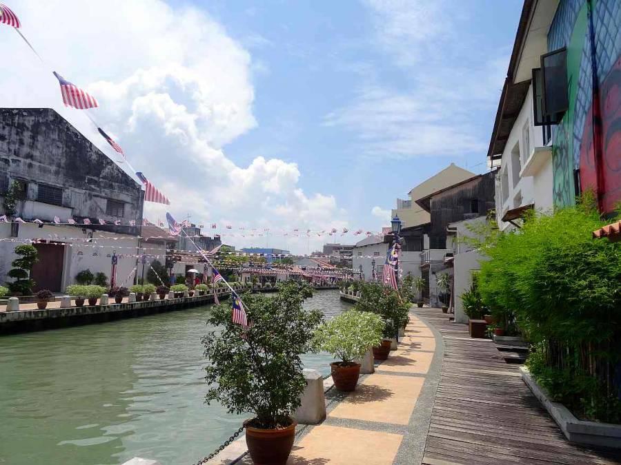 Malaysia | Melaka River lädt bei Sonnenschin zum Spaiergang entlang der Promenade ein. Bunte Häuser, einige grüne bonsaiartige Pflanzen und aufgehängte Malaysia Fahnen säumen den Weg
