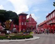 Malaysia | Zentrum der Stadt, der Roter Platz in Melaka. Rote Häuser und die Melaka Kirche aus der Kolonialzeit, Touristen und eine runde Blumeninsel mit Wegweisern in verschiedene Länder. Eine der Top-Sehenswürdigkeiten