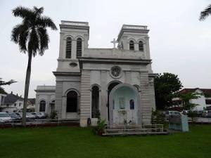 Malaysia   Mariä Himmelfahrts Kirche in George Town, Penang. Graue unscheinbare Steinmauern, eine Palme auf einer grünen Wiese