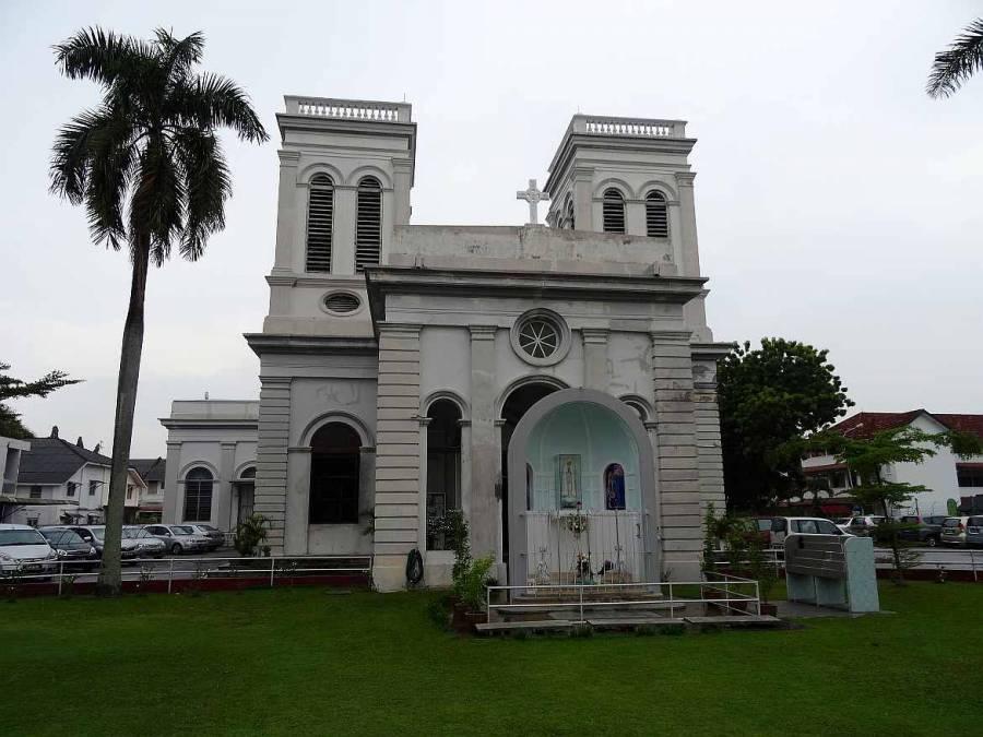 Malaysia | Mariä Himmelfahrts Kirche in George Town, Penang. Graue unscheinbare Steinmauern, eine Palme auf einer grünen Wiese