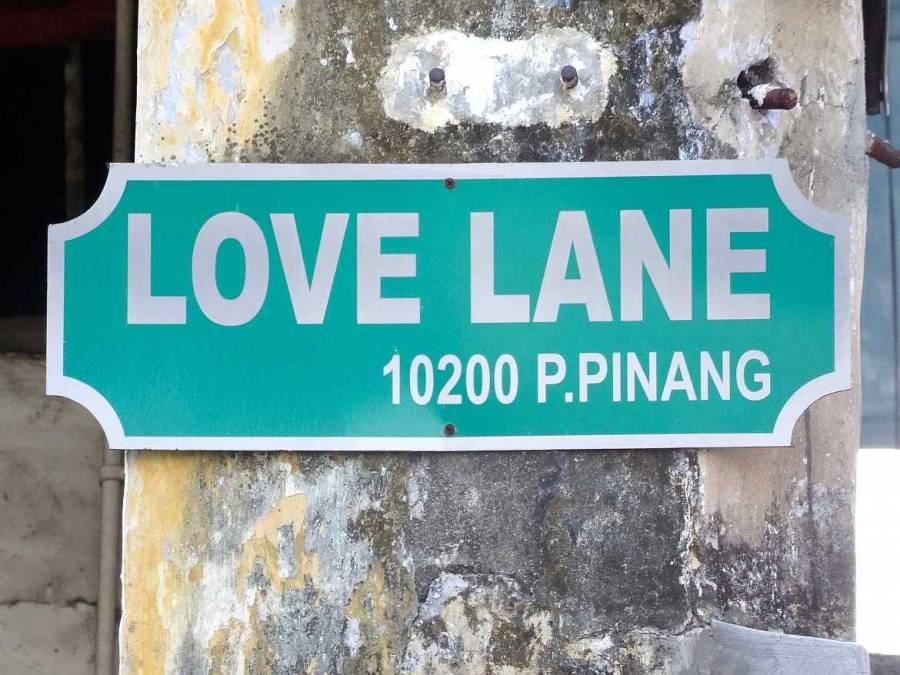 Malaysia | Grünes mit weißer Schrift an eine Steinmauer befestigtes Straßenschild der Love Lane dem Backpacker Viertel in George Town, Penang