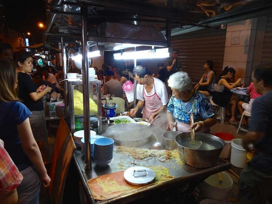Malaysia | Nachtmarkt in George Town, Penang. Brodelnde Töpfe und Verkäufer vor einem Rollwagen auf der Straße kochend und hungrige Asiaten.