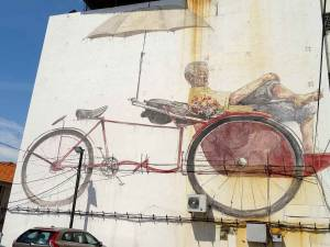 Malaysia | An eine Hauswand gezeichnete Straßenkunst in George Town, Penang. Ein Mann sitzt unter einem Schirm auf seiner Fahrradrikscha