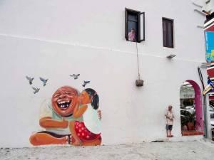 Malaysia | Straßenkunst in George Town, Penang. Ein Mädchen sitzt auf Opas Schoß und flüstert Ihm etwas ins Ohr, so dass dass dieser lächelt; Tauben kreisen über deren Köpfe. Eine Frau steht am offenen Fester im ersten Stock, in der Hand einen Korb der an einem Seil befestigt ist. Ein an der Straßenecke stehender Mann schaut zu ihr nach oben