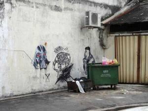 Malaysia | Straßenkunst in George Town, Penang. Drei verschiedenen Karikaturen von gruseligen Männerköpfen auf eine steinernen Hauswand gezeichnet. Im Vordergrund ein alter mit Müll beladener kleiner Anhänger und eine grüne vollgestopfte Mülltonne